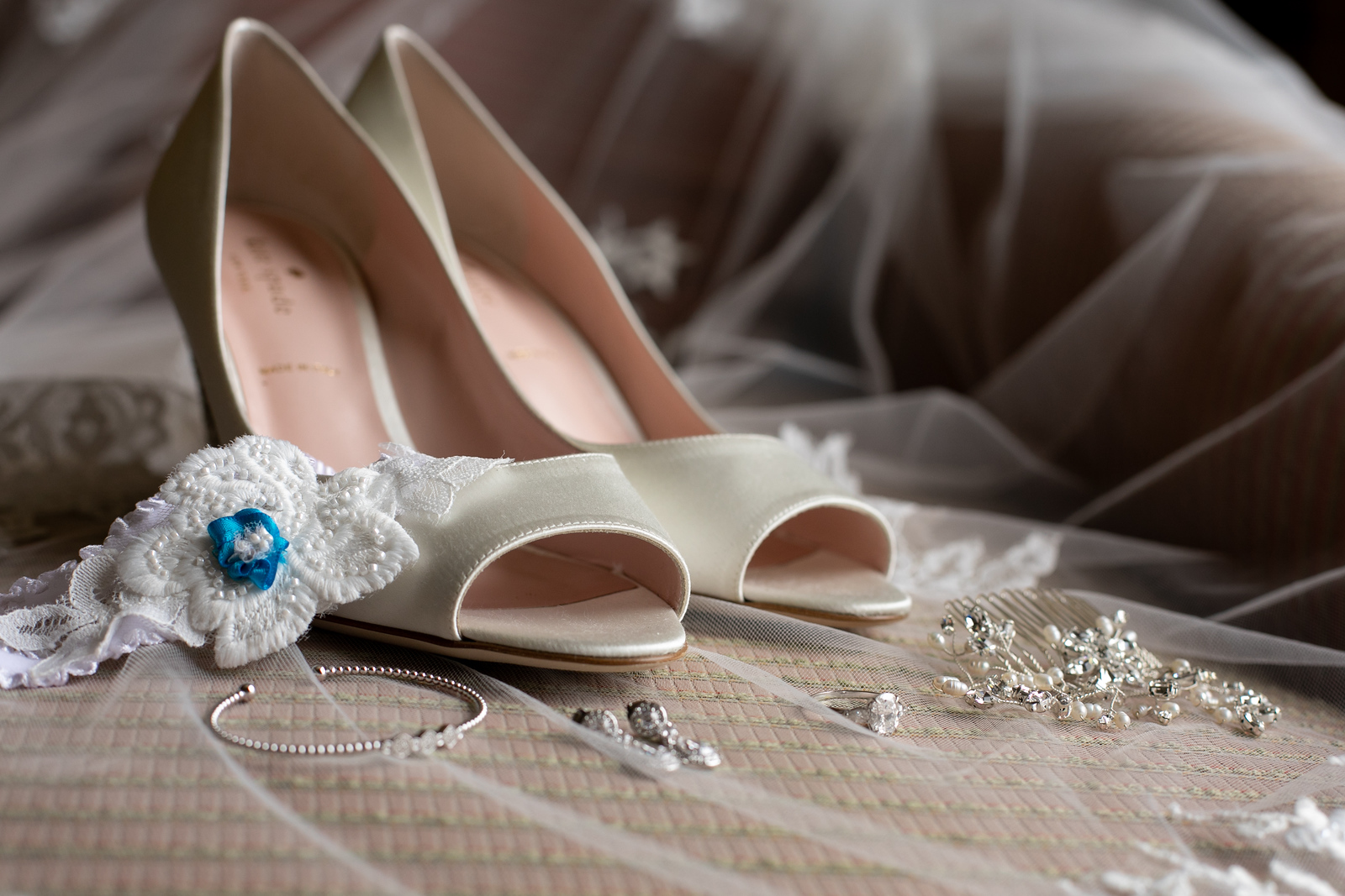 cream colored wedding high heeled shoes with a white and blue garter atop a wedding vial with the bride's jewelry