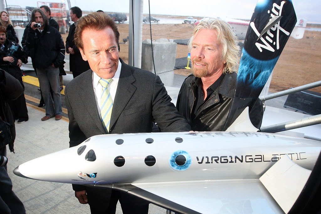 . California Gov. Arnold Schwarzenegger (L) and Sir Richard Branson stand next to a model as Virgin Galactic unveils its new SpaceShipTwo spacecraft at the Mojave Spaceport on December 7, 2009 near Mojave, California.   (Photo by David McNew/Getty Images)