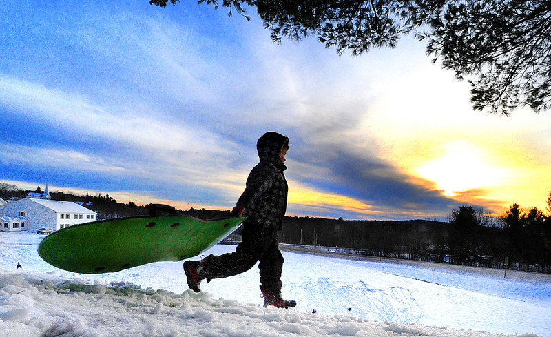 Austin Powell, 8, of Turner, runs to find a better spot on the hill while sledding in Turner next to the Calvary Baptist Church.