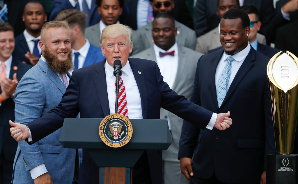 . President Donald Trump points out Clemson linebacker Ben Boulware, left, and lineman Carlos Watkins, during a ceremony on the South Lawn of the White House in Washington, Monday, June 12, 2017, where he honored the 2016 NCAA Football National Champions Clemson University Tigers. (AP Photo/Pablo Martinez Monsivais)
