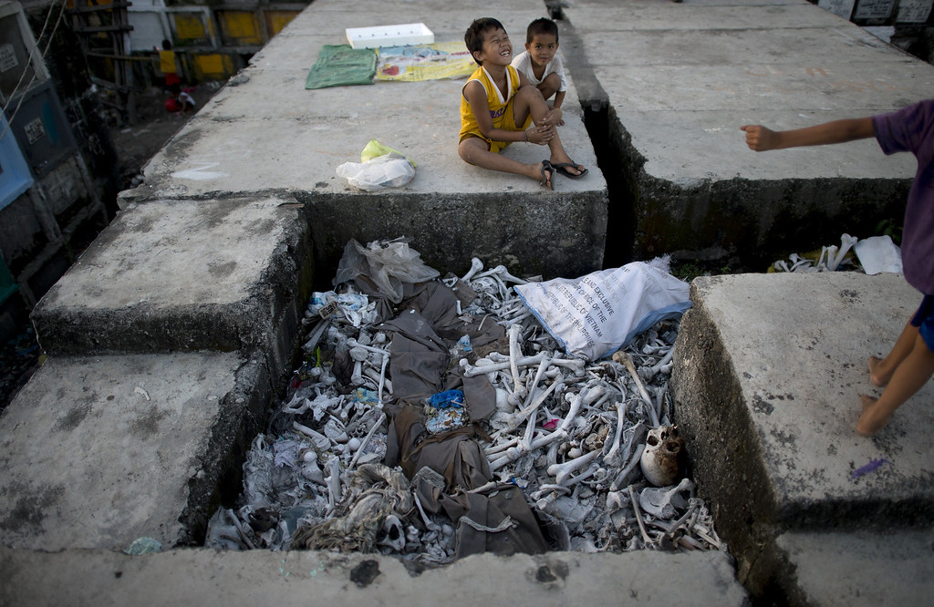 . Children living inside the cemetery play near human bones on top of stacked graves at the Navotas Public Cemetery in Manila on October 31, 2014, days ahead of the traditional All Souls\' day. Millions across the Philippines will visit cemeteries to pay their respects to their dead, in an annual tradition that combines catholic religious rites with the country\'s penchant for festivity. AFP PHOTO/NOEL CELIS/AFP/Getty Images
