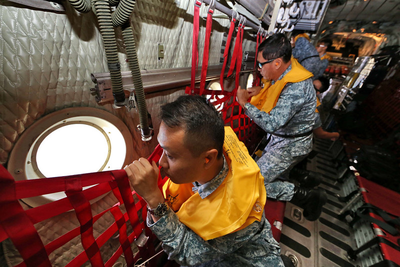 . This photo taken by the Lianhe Zaobao newspaper and made available on December 29, 2014 shows Republic of Singapore Air Force personnel (RSAF) servicemen on board a C-130 aircraft participating in the search and locate (SAL) operation for missing AirAsia flight QZ8501 at sea.  The AirAsia plane with 162 people on board went missing en route from Indonesia to Singapore early on December 28, officials and the airline said, in the third major incident to affect a Malaysian carrier this year.  AFP PHOTO/KWONG KC /Lianhe Zaobao