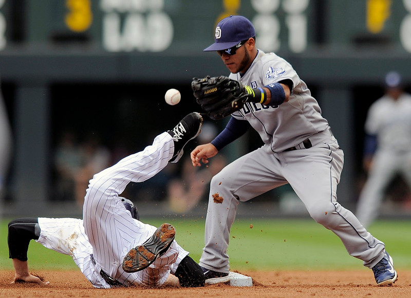 . San Diego Padres shortstop Alexi Amarista, right, bobbles the ball as Colorado Rockies\' Ben Paulsen, left, dives safely back to second base on a pickoff play in the second inning of a baseball game Sunday, Sept. 7, 2014, in Denver. (AP Photo/Chris Schneider)