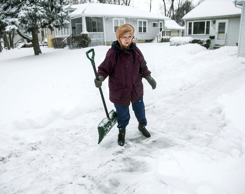 . Violet Malkowski, 81, stands in her driveway in Champaign, Ill., on Wednesday, Feb. 5, 2014. Malkowski said this was her third try at clearing the driveway this morning. (AP Photo/The News-Gazette, John Dixon)