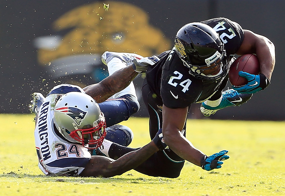 . Kyle Arrington #24 of the New England Patriots tackles  Montell Owens #24 of the Jacksonville Jaguars during the game at EverBank Field on December 23, 2012 in Jacksonville, Florida.  (Photo by Sam Greenwood/Getty Images)