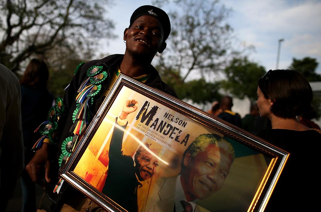 . A vendor sells a framed image of Nelson Mandela outside of Mandela\'s home on December 7, 2013 in Johannesburg, South Africa.  (Photo by Justin Sullivan/Getty Images)