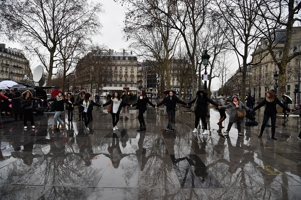. The wet pavement reflects the images of people as they hold hands and form a circle around the Place de la Republique at midday in solidarity with victims of yesterday\'s terrorist attack on January 8, 2015 in Paris, France.  Twelve people were killed including two police officers as two gunmen opened fire at the offices of the French satirical publication Charlie Hebdo on January 7.  (Photo by Pascal Le Segretain/Getty Images)