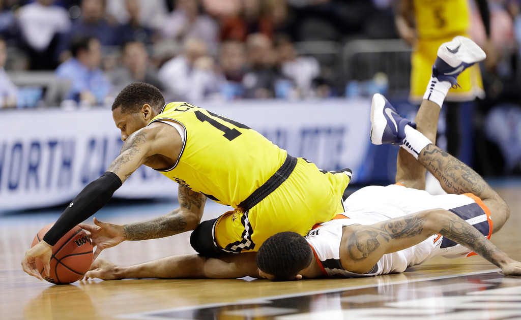 . UMBC\'s Jairus Lyles (10) falls on top of Virginia\'s Isaiah Wilkins as they chase the ball during the first half of a first-round game in the NCAA men\'s college basketball tournament in Charlotte, N.C., Friday, March 16, 2018. (AP Photo/Gerry Broome)