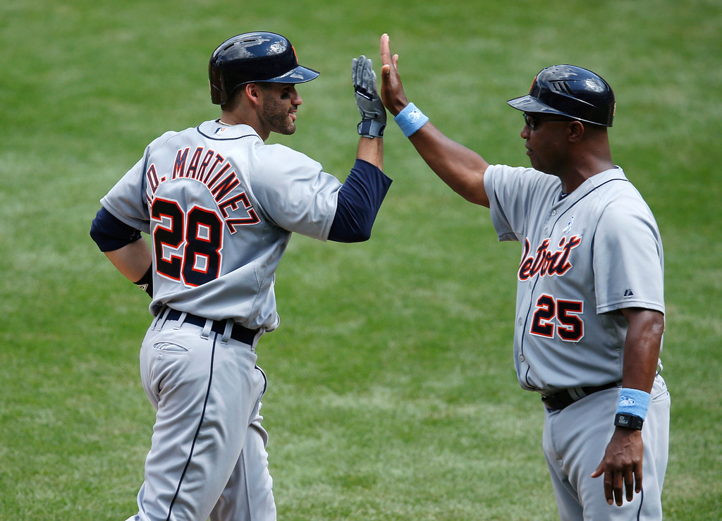 . Detroit Tigers J.D. Martinez (28) slaps palms Detroit Tigers third base coach Dave Clark (25) after hitting a sixth-inning, three-run home run off New York Yankees relief pitcher Danny Burawa in a baseball game at Yankee Stadium in New York, Sunday, June 21, 2015.  (AP Photo/Kathy Willens)