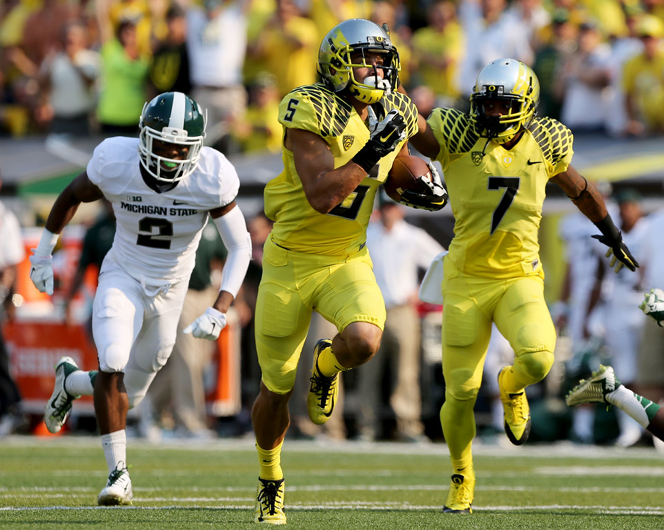 . With Michigan State\'s Darian Hicks, left, in pursuit, Oregon\'s Devon Allen, center, runs to the end zone with teammate Keanon Lowe providing blocking during the 2nd quarter of their college football game in Eugene, Oregon, Saturday Sept. 6, 2014. (AP Photo/Chris Pietsch)