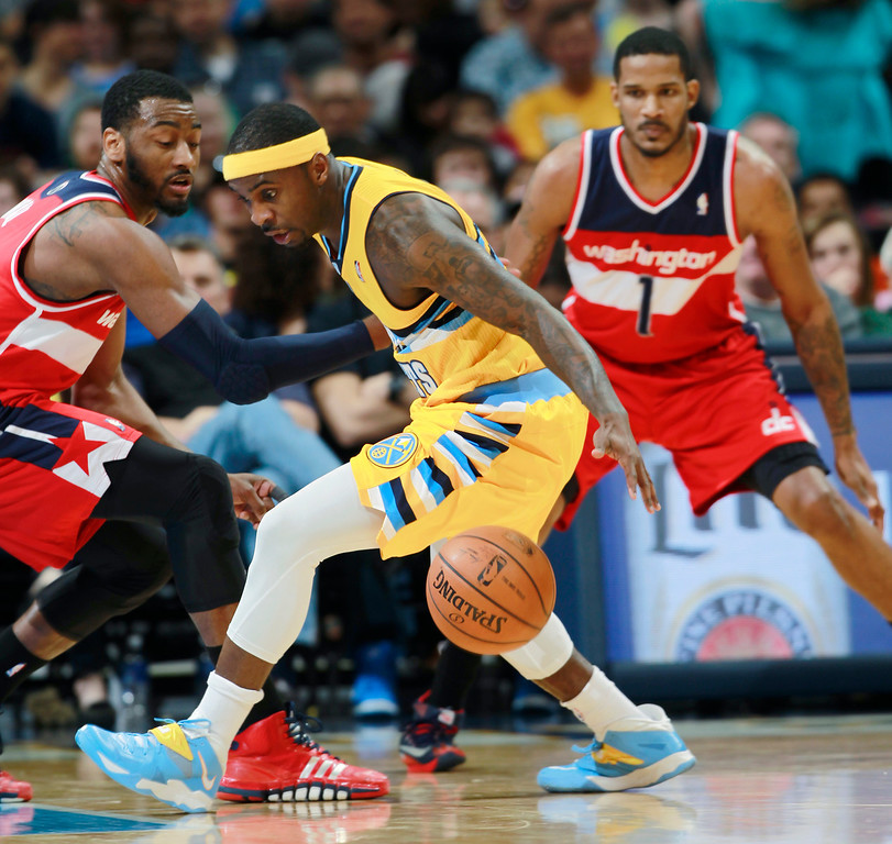 . Denver Nuggets guard Ty Lawson, center, loses control of the ball as Washington Wizards guard John Wall, left, and forward Trevor Ariza cover in the first quarter of an NBA basketball game in Denver on Sunday, March 23, 2014. (AP Photo/David Zalubowski)