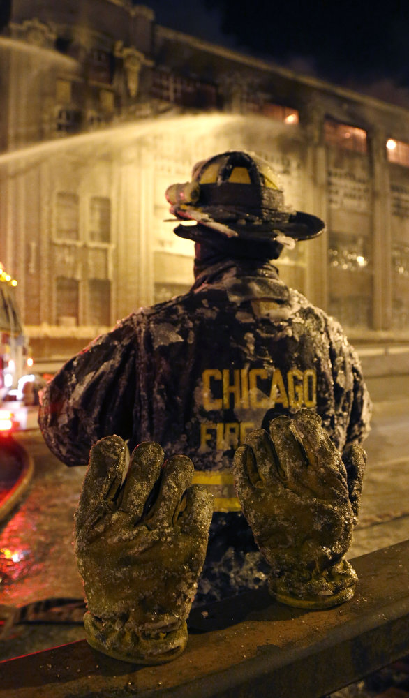 . The frozen ice covered pair of gloves belonging to a Chicago firefighter stand on a railing behind him in single digit temperatures during a five-alarm blaze in a warehouse on the city\'s South Side, Bridgeport neighborhood rages Wednesday, Jan. 23, 2013, in Chicago. (AP Photo/Charles Rex Arbogast)