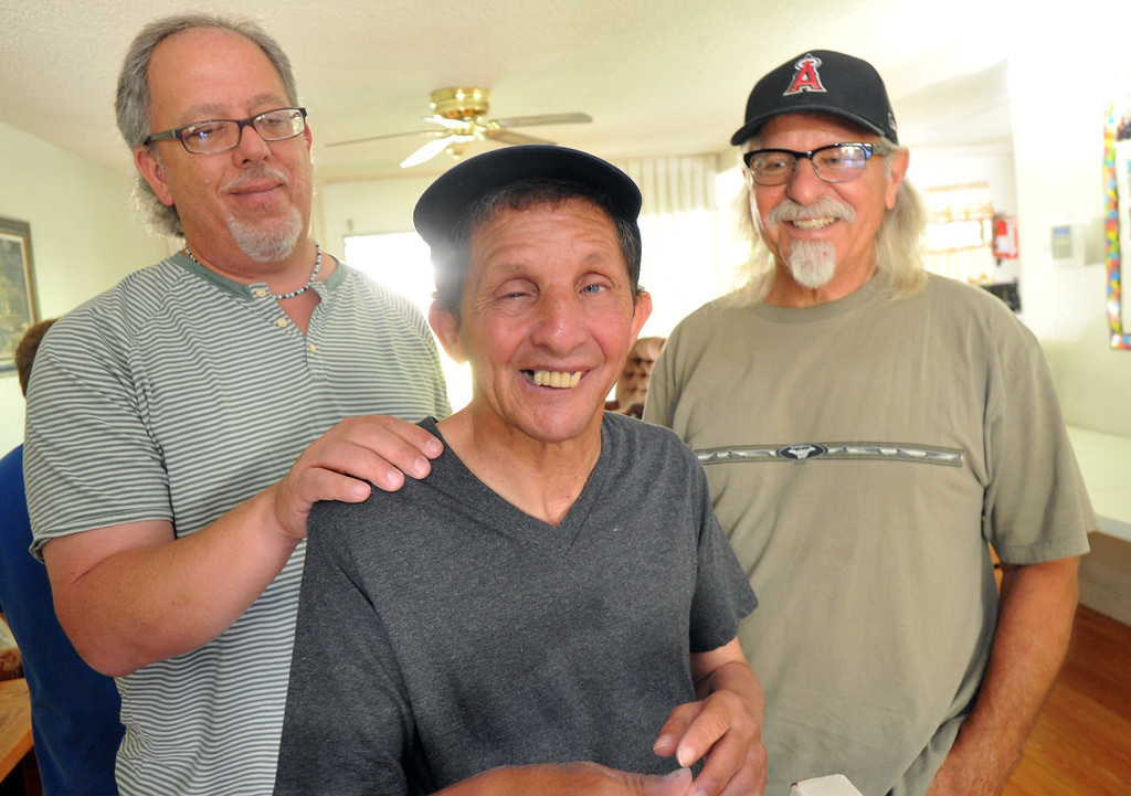 . Gary Borack, 58, is joined by his brothers, Hohn, left, and Robert, right, at his group home in Mission Viejo on Wednesday June 26, 2013. Gary Borack, who was diagnosed with severe mental retardation at the age of 5, recently transitioned out of Lanterman Developmental Center in Pomona about 9 months ago, and is living successfully in the group home. (SGVN/Staff Photo by Keith Durflinger)
