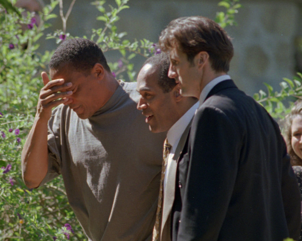 . O.J. Simpson, center, walks into his home in the Brentwood section of Los Angeles, Calif., with his friend, Al Cowlings, left and an unidentified man after he was acquitted of the double-murder of his ex-wife Nicole Brown and Ronald Goldman in Los Angeles Tuesday, Oct. 3, 1995.(AP Photo/Reed Saxon)