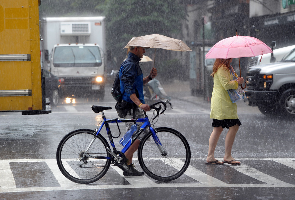 . People on Lexington Avenue cross East 88th Street in a heavy rain June 13, 2013 in New York as a severe storm affects the northeastern US. AFP PHOTO/Stan  HONDA/AFP/Getty Images