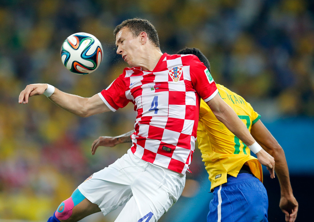 . Croatia\'s Ivan Perisic, front, goes for a header as Brazil\'s Luiz Gustavo, rear, defends during the group A World Cup soccer match in the opening game of the tournament at Itaquerao Stadium in Sao Paulo, Brazil, Thursday, June 12, 2014. (AP Photo/Frank Augstein)