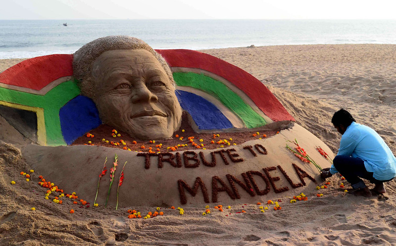 . Indian sand artist Sudarsan Pattnaik places flowers on a sand sculpture he made in tribute to former South African president Nelson Mandela at the Golden Sea Beach in Puri, some 65 kilometers away from Bhubaneswar, on December 6, 2013. Mandela, the revered icon of the anti-apartheid struggle in South Africa and one of the towering political figures of the 20th century, has died aged 95. Mandela, who was elected South Africa\'s first black president after spending nearly three decades in prison, had been receiving treatment for a lung infection at his Johannesburg home since September, after three months in hospital in a critical state. ASIT KUMAR/AFP/Getty Images