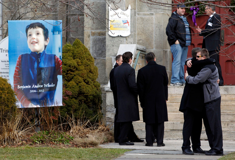 Description of . Mourners embrace outside of Trinity Episcopal Church while standing next to a portrait of Benjamin Andrew Wheeler, one of the students killed in the Sandy Hook Elementary School shooting last week, Thursday, Dec. 20, 2012, in Newtown, Conn. Wheeler, 6, died when the gunman, Adam Lanza, walked into Sandy Hook Elementary School in Newtown, Dec. 14, and opened fire, killing 26 people, including 20 children, before killing himself. (AP Photo/Julio Cortez)
