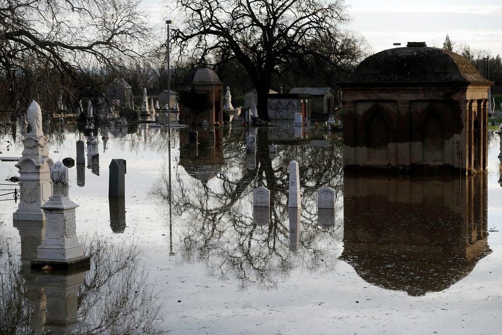 . Graves are submerged in floodwaters at a cemetery downstream from a damaged dam Wednesday, Feb. 15, 2017, in Marysville, Calif. The Oroville Reservoir is continuing to drain Wednesday as state water officials scrambled to reduce the lake\'s level ahead of impending storms. (AP Photo/Marcio Jose Sanchez)