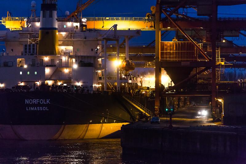 Hansaport Hamburg mit Massengutfrachter am Abend