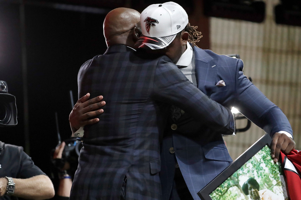 . UCLA\'s Takkarist McKinley, right, hugs Deon Sanders after McKinley was selected by the Atlanta Falcons during the first round of the 2017 NFL football draft, Thursday, April 27, 2017, in Philadelphia. (AP Photo/Julio Cortez)