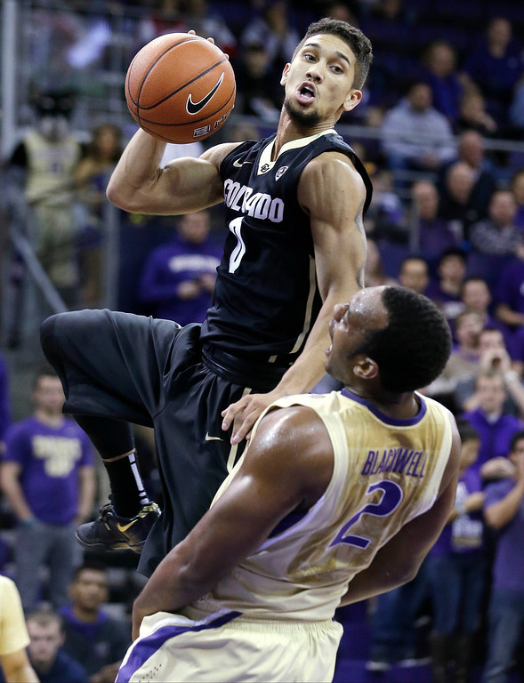 . Colorado\'s Askia Booker (0) crashes into Washington\'s Perris Blackwell whille shooting in the first half of an NCAA college basketball game on Sunday, Jan. 12, 2014, in Seattle. (AP Photo/Elaine Thompson)