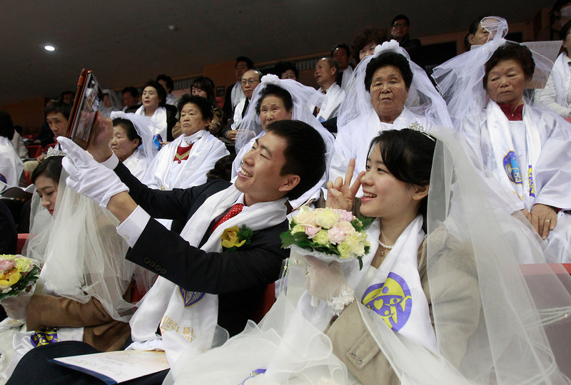 . A newly-married couple takes pictures before a mass wedding ceremony at the CheongShim Peace World Center in Gapyeong, South Korea, Wednesday, Feb. 12, 2014. Some 2,500 South Korean and foreign couples exchanged or reaffirmed marriage vows in the Unification Church\'s mass wedding arranged by Hak Ja Han Moon, wife of the late Rev. Sun Myung Moon, the controversial founder of the Unification Church. (AP Photo/Lee Jin-man)