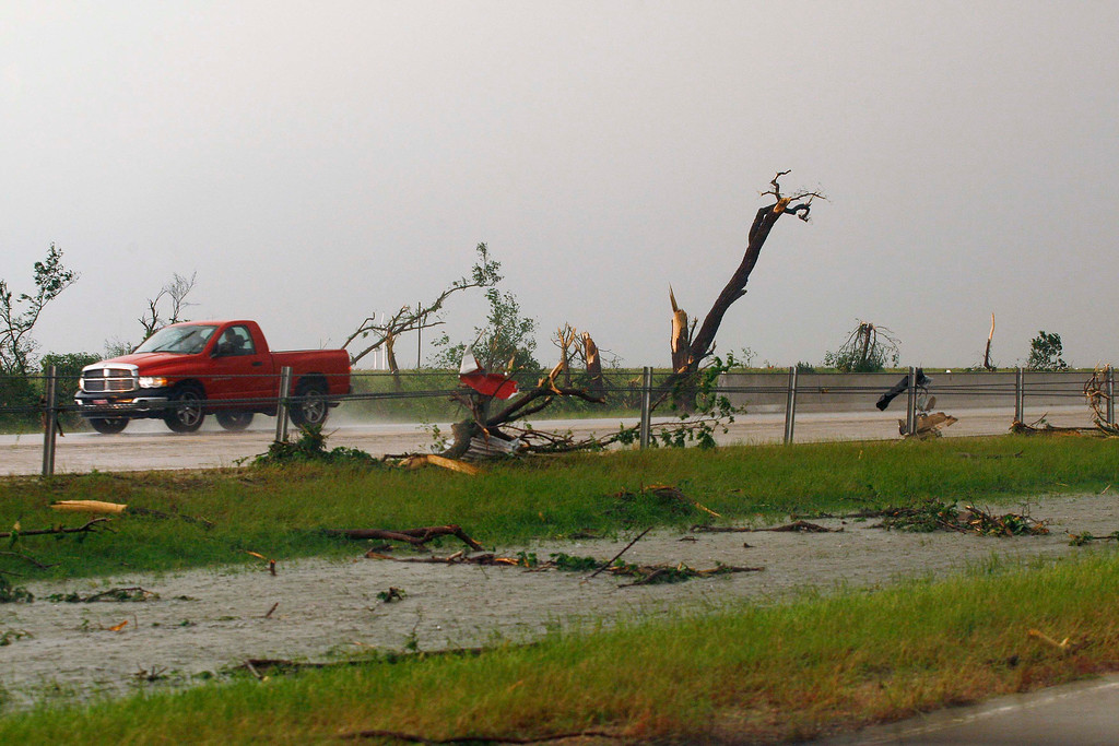 . A pickup passes by tornado debris in the Westbound lane of Interstate-40, just east of El Reno, Oklahoma May 31, 2013.  Violent thunderstorms spawned tornadoes that menaced Oklahoma City and its already hard-hit suburb of Moore on Friday, killing a mother and her baby, and officials worried that drivers stuck on freeways could be trapped in the path of dangerous twisters. One twister touched down on Interstate 40 and was headed toward Oklahoma City.  REUTERS/Bill Waugh