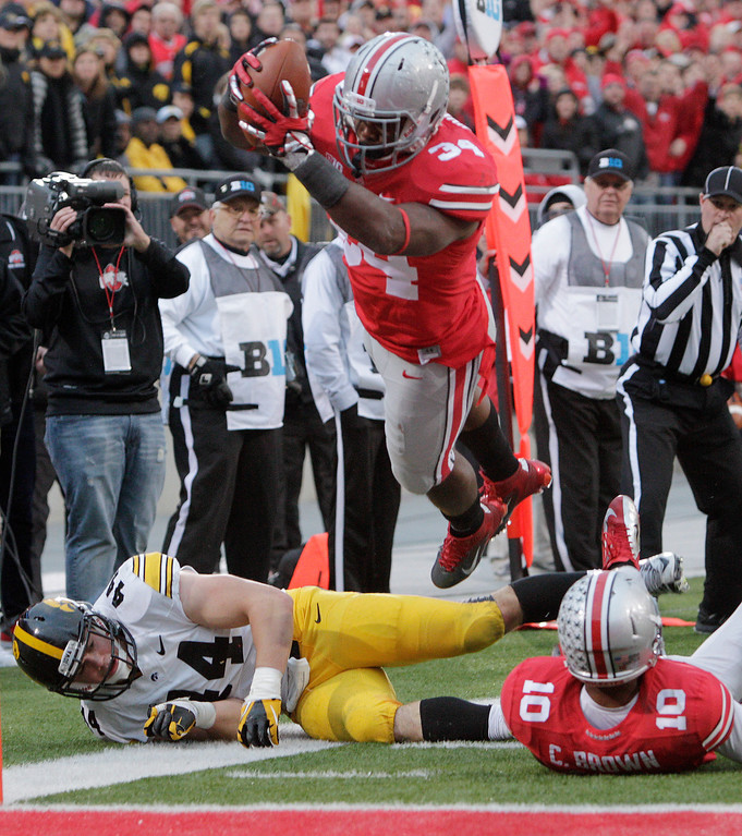 . Ohio State running back Carlos Hyde, top, dives over the goal line to score a touchdown past teammate Corey Brown, right, and Iowa linebacker James Morris during the fourth quarter of an NCAA college football game Saturday, Oct. 19, 2013, in Columbus, Ohio. Ohio State beat Iowa 34-24. (AP Photo/Jay LaPrete)