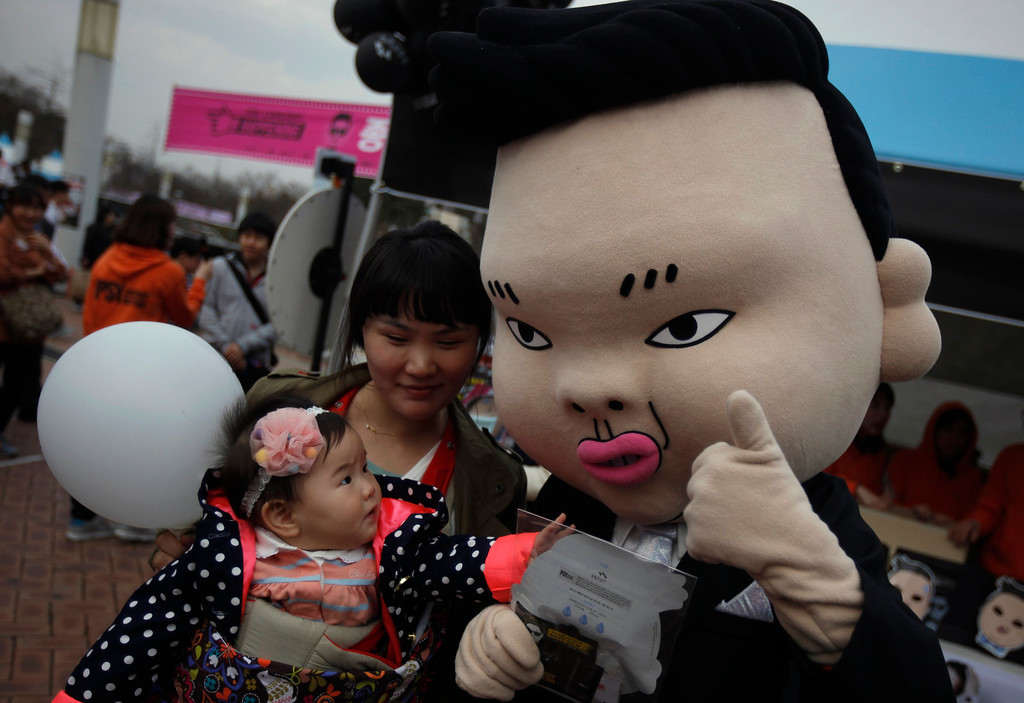 """. A baby looks at a mask of South Korean rapper Psy at the Seoul World Cup stadium, where is venue for the Psy\'s concert \""""happening\"""" in Seoul April 13, 2013. Psy will perform \""""Gentleman\"""" in public for the first time on Saturday at a concert at Seoul\'s World Cup stadium but he has been coy about what dance to expect this time, except to hint that it is based on traditional Korean moves. Psy released his new single on Thursday hoping to repeat the success of \""""Gangnam Style\"""" that made him the biggest star to emerge from the growing K-pop music scene.   REUTERS/Kim Hong-Ji"""
