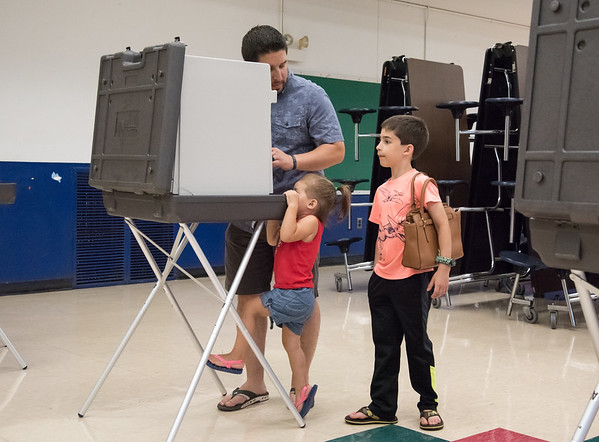08/14/18 Wesley Bunnell | Staff Derek Williams votes at the Slade Middle School voting station on Tuesday evening as daughter Alana, age 2, and Titus holding his mothers purse, age 8, look on.