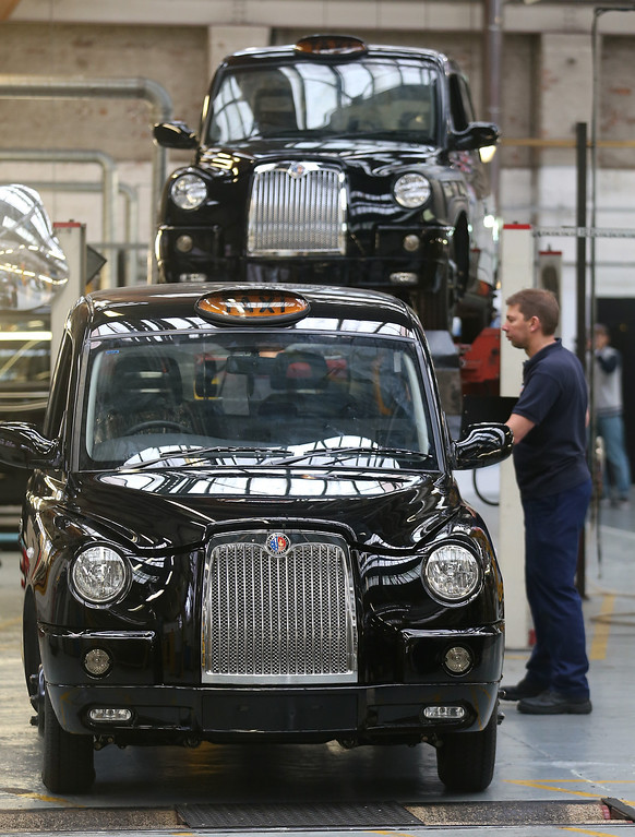 . COVENTRY, ENGLAND - SEPTEMBER 11:  Workers inside the factory of The London Taxi Company inspect a completed TX4 (Euro 5) London Taxi on September 11, 2013 in Coventry, England.   (Photo by Matt Cardy/Getty Images)