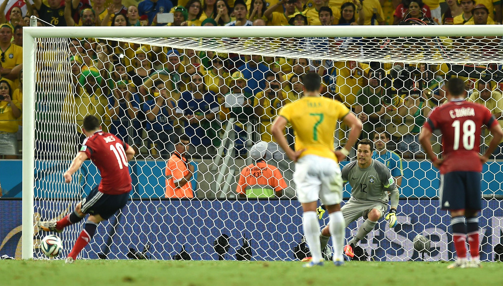 . Colombia\'s midfielder James Rodriguez (L) shoots and scores a penalty during the quarter-final football match between Brazil and Colombia at the Castelao Stadium in Fortaleza during the 2014 FIFA World Cup on July 4, 2014.   VANDERLEI ALMEIDA/AFP/Getty Images