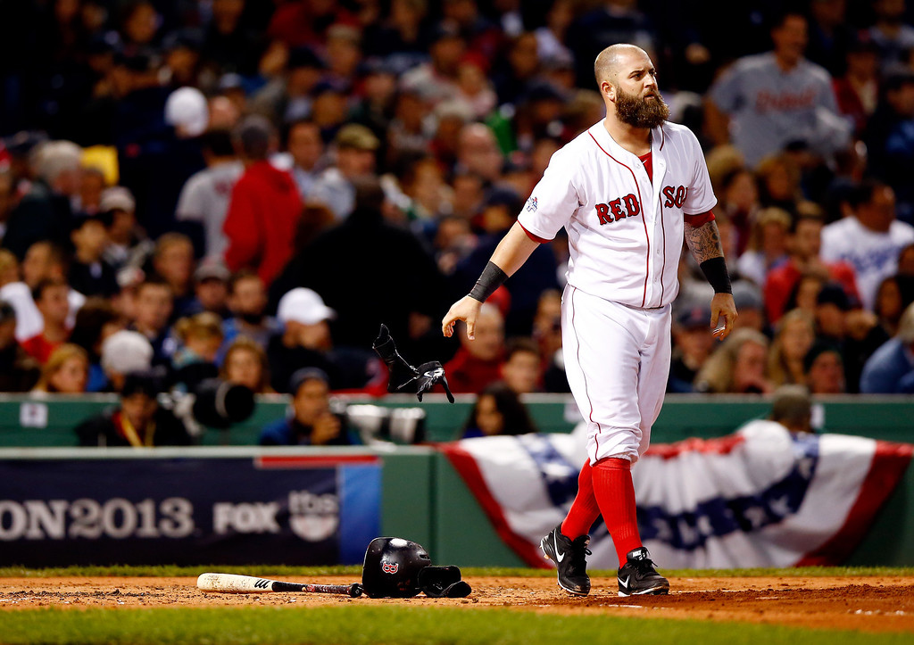 . BOSTON, MA - OCTOBER 12: Mike Napoli #12 of the Boston Red Sox drops his gloves after striking out in the first inning against the Detroit Tigers during Game One of the American League Championship Series at Fenway Park on October 12, 2013 in Boston, Massachusetts.  (Photo by Jared Wickerham/Getty Images)