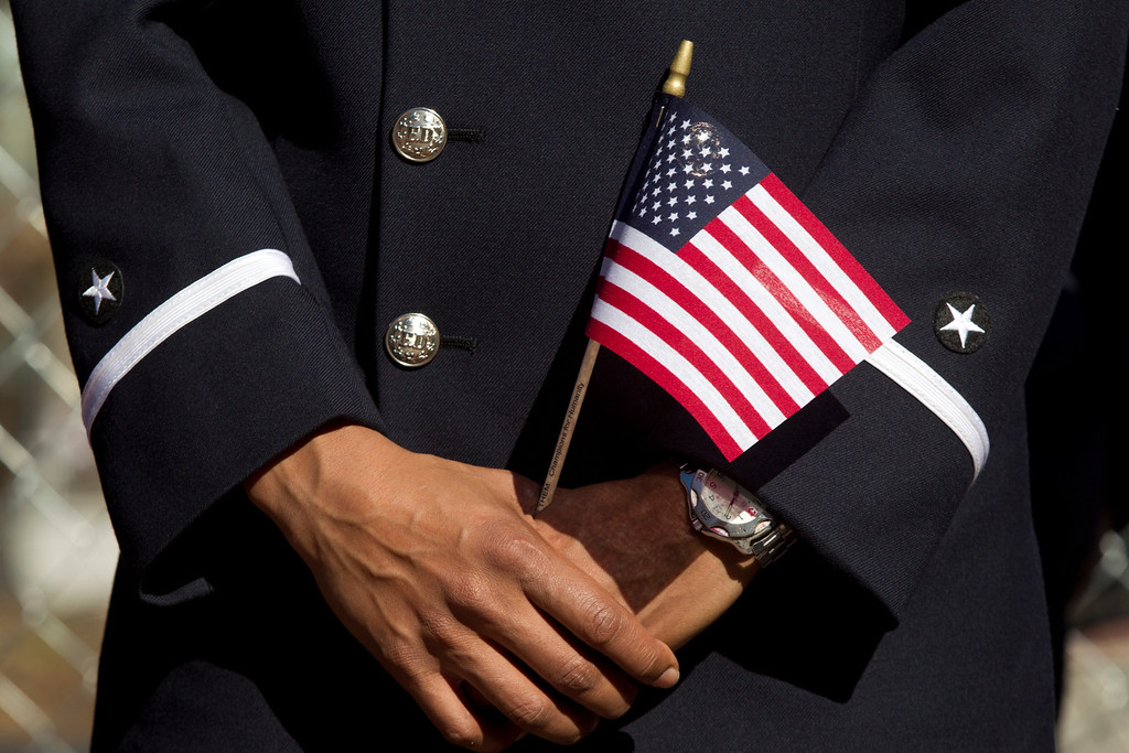 """. An Oakland firefighter holds an American flag at a ceremony to dedicate the final section of \""""Remember Them,\"""" artist Mario Chiodo\'s paean to heroes of civil rights and humanity, Thursday, Feb. 21, 2013 in Oakland Calif. (D. Ross Cameron/Staff)"""