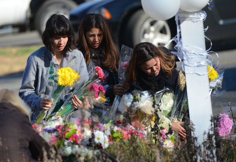 Description of . Residents pay  flower tributes to the victims of an elementary school shooting in Newtown, Connecticut, on December 15, 2012. A young gunman slaughtered 20 small children and six teachers on December 14 after walking into a school in an idyllic Connecticut town wielding at least two sophisticated firearms.     EMMANUEL DUNAND/AFP/Getty Images