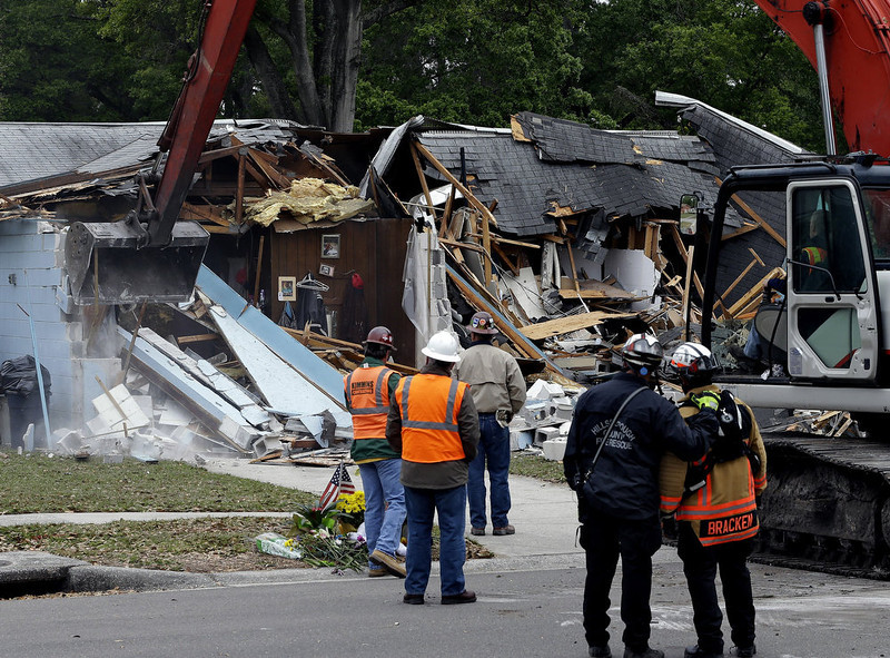 . Demolition experts watch as the home of Jeff Bush, 37,  is destroyed Sunday, March 3, 2013, after a sinkhole opened up underneath it late Thursday evening swallowing Bush, 37, in Seffner, Fla. The 20-foot-wide opening of the sinkhole was almost covered by the house, and rescuers said there were no signs of life since the hole opened Thursday night. (AP Photo/Chris O\'Meara)