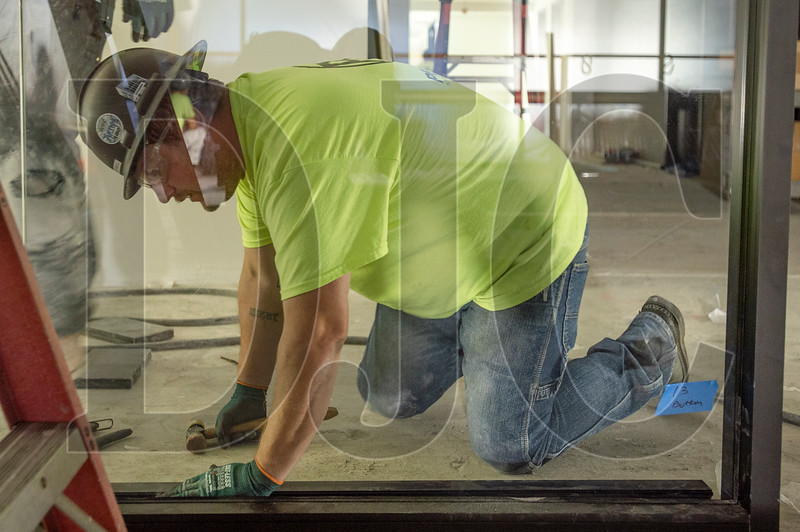 Michael Dowell, a journeyman glazier with Local 740 and Culver Glass, installs a storefront window. (Josh Kulla/DJC)