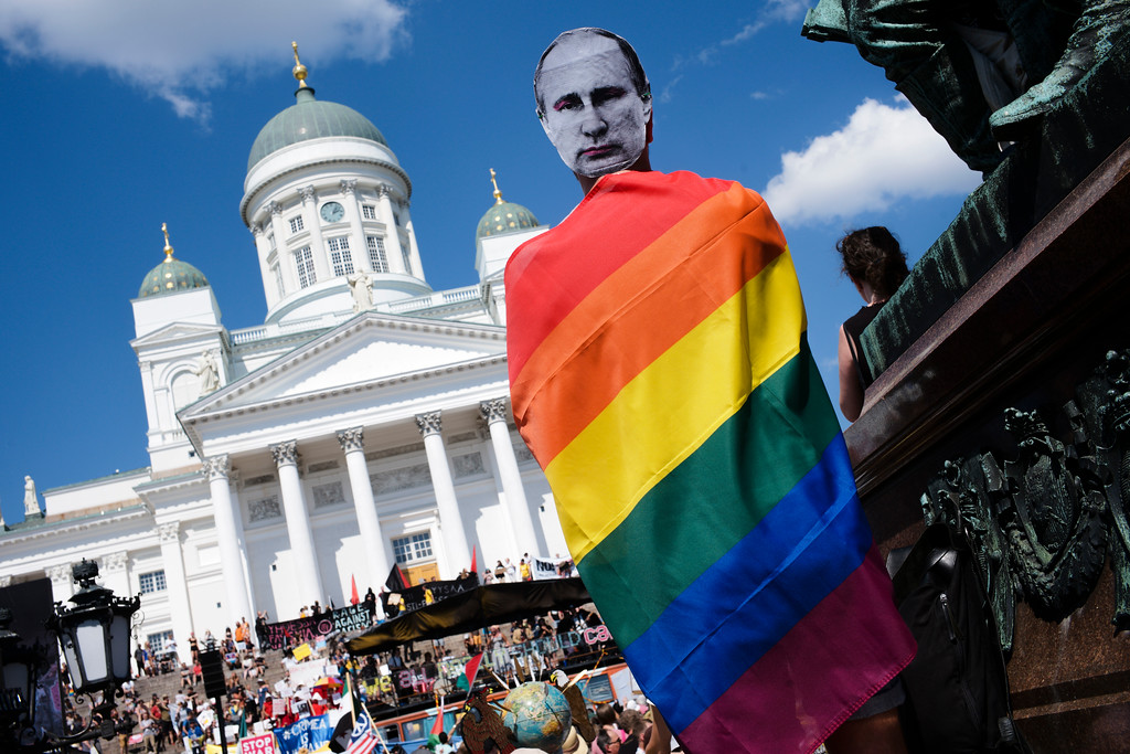 . A man with a Putin mask and a rainbow flag attends a rally against the policy of U.S. President Donald Trump and Russian President Vladimir Putin in central Helsinki, Sunday, July 15, 2018. President Trump and President Putin will meet in Finland\'s capital on Monday, July 16, 2018. (AP Photo/Markus Schreiber)
