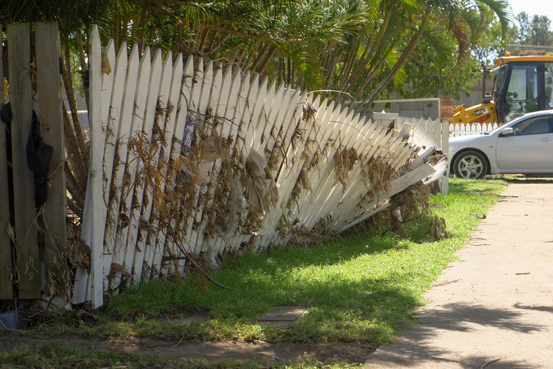 Front garden fences covered with debris, and then pushed over by the force of the flowing river.