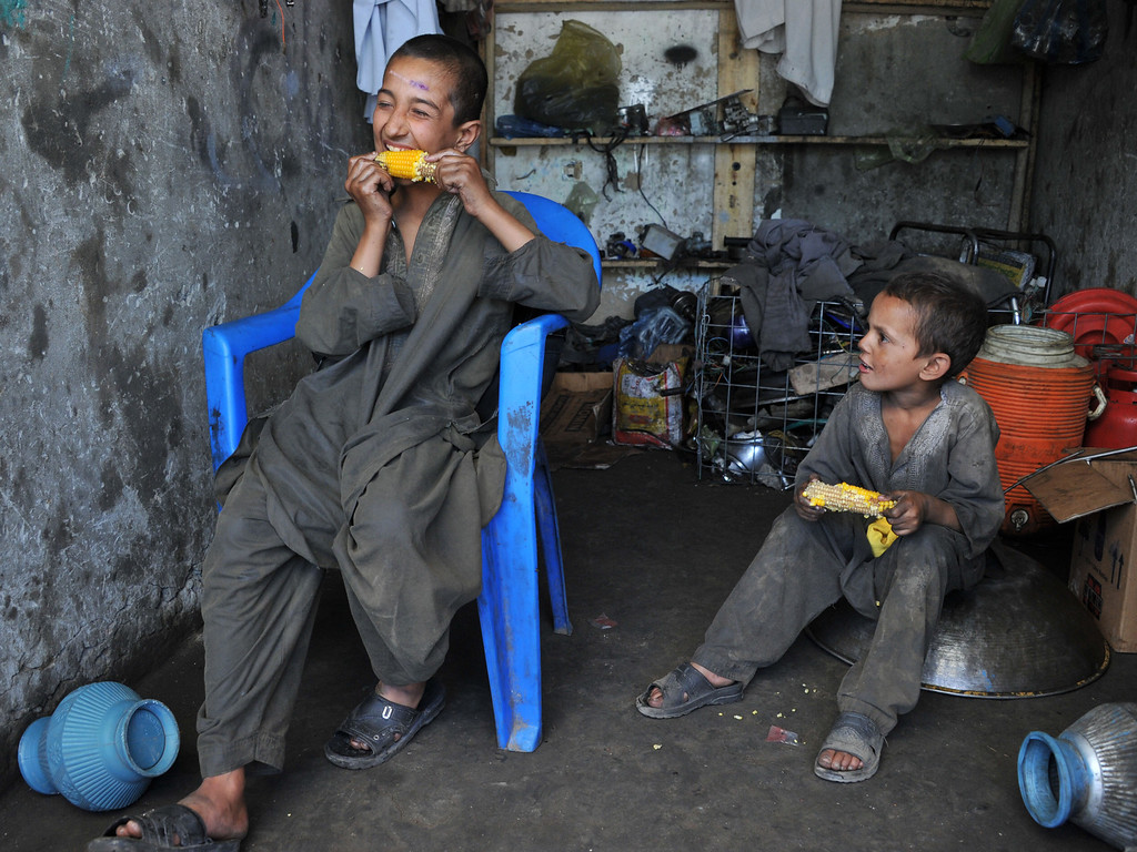 . Afghan child labourers eat corn while taken a break at a motorcycle mechanic shop in Jalalabad, eastern Nangarhar province, during Children\'s Day on June 1, 2013. Tens of thousands of children in Afghanistan, driven by poverty, work on the streets of the war-torn country\'s cities and often fall prey to Taliban bombings and other violence, as well as abuse. Noorullah Shirzada/AFP/Getty Images