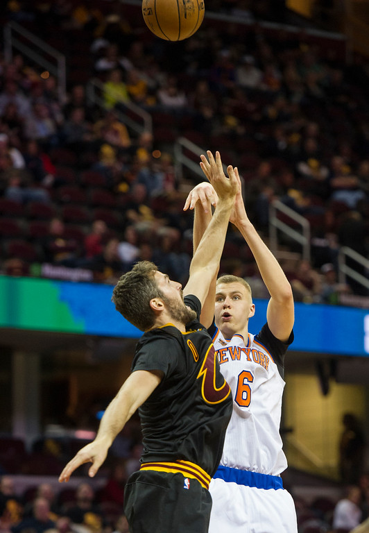 . New York Knicks\' Kristaps Porzingis (6) shoots over Cleveland Cavaliers\' Kevin Love (0) during the second half of a basketball game in Cleveland, Tuesday, Oct. 25, 2016. Cleveland won 117-88.(AP Photo/Phil Long)