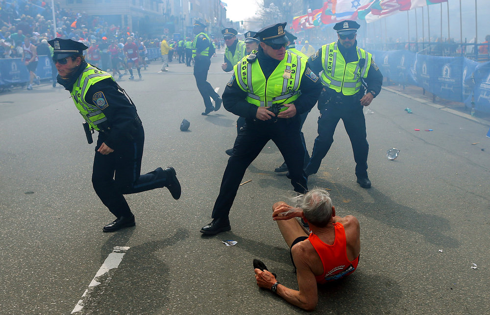 . Police officers react to a second explosion at the finish line of the Boston Marathon in Boston, Monday, April 15, 2013. Two explosions shattered the euphoria of the Boston Marathon finish line on Monday, sending authorities out on the course to carry off the injured while the stragglers were rerouted away from the smoking site of the blasts. (AP Photo/The Boston Globe,  John Tlumacki)