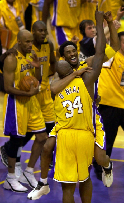 . Los Angeles Lakers\' Kobe Bryant and Shaquille O\'Neal hug and lift their arms in victory after taking the NBA Championship in six games with a 116-111 win over the Indiana Pacers in Los Angeles Monday, June 19, 2000. (AP Photo/Michael Caulfield)