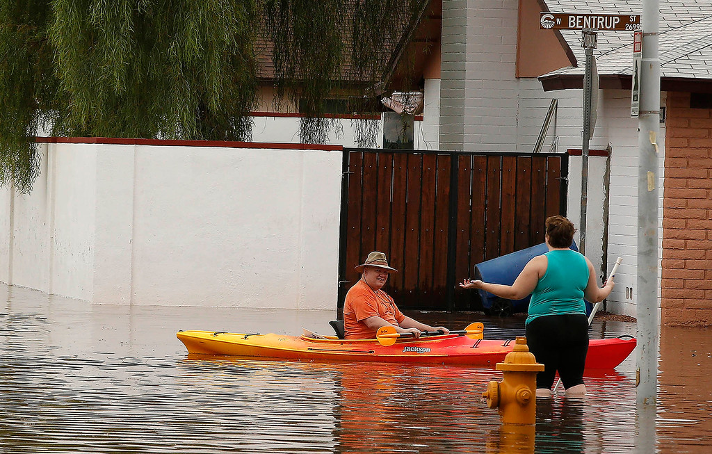 . Two residents of a Chandler neighborhood talk in a flooded street after record breaking rains closed streets, highways and schools Monday, Sept. 8, 2014, in Chandler, Ariz. (AP Photo/Darryl Webb)