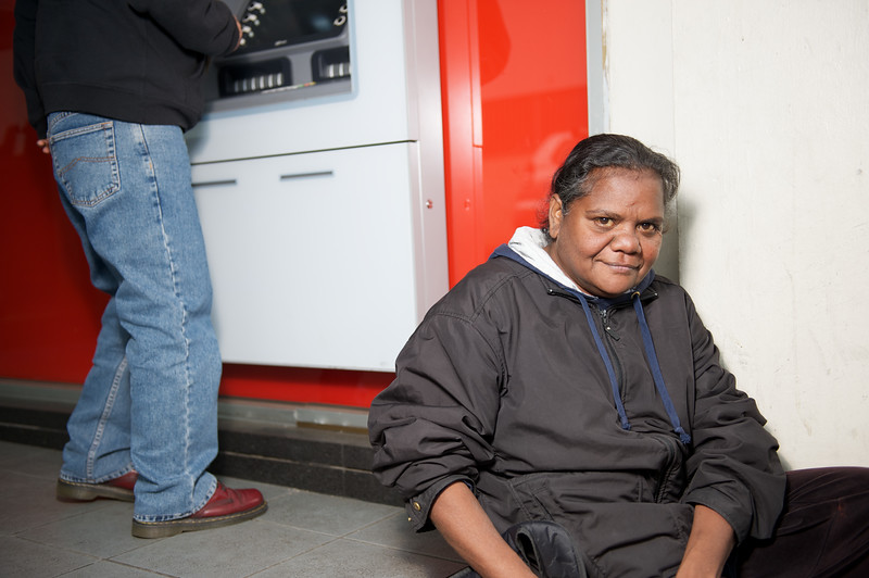 Aboriginal woman sitting by an automatic teller machine, looking at camera.
