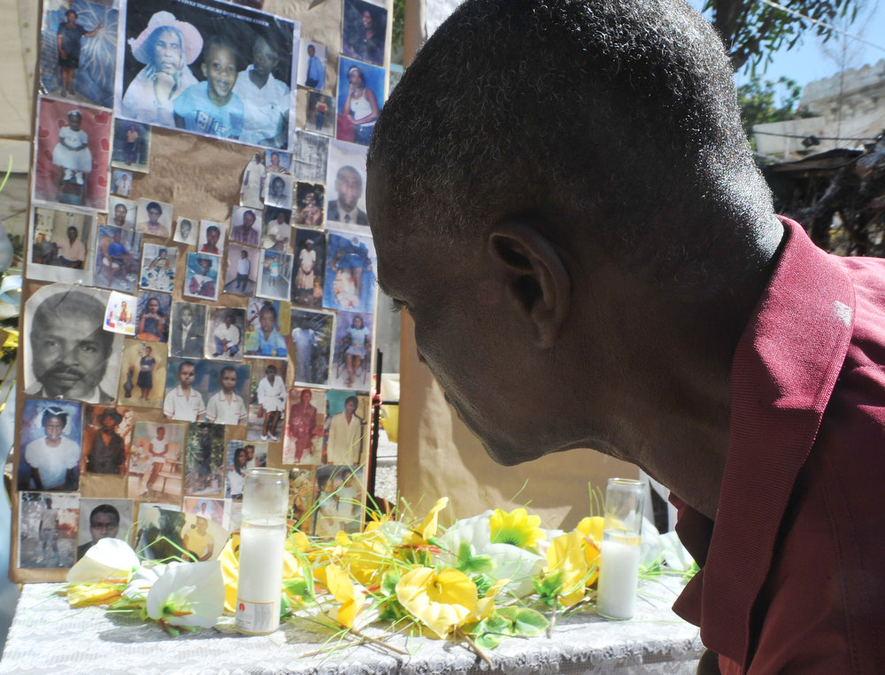 Description of . A man pays his respects at a makeshift memorial for victims of the January 12, 2010 Haiti earthquake near the destroyed Cathedral of Port-au-Prince on January 12, 2013. Three years after a massive earthquake ravaged Haiti, President Michel Martelly said the country was slowly rebuilding, despite the ongoing day-to-day misery of many survivors.  An estimated 250,000 people were killed in the January 12, 2010 earthquake. Hundreds of thousands are still living rough in squalid makeshift camps, and they now face rampant crime, a cholera outbreak and the occasional hurricane.during memorial day in honor of the victims of the last quake of January 12 2013 in Haiti.People put photo of parent and friend victims of the quake. THONY BELIZAIRE/AFP/Getty Images