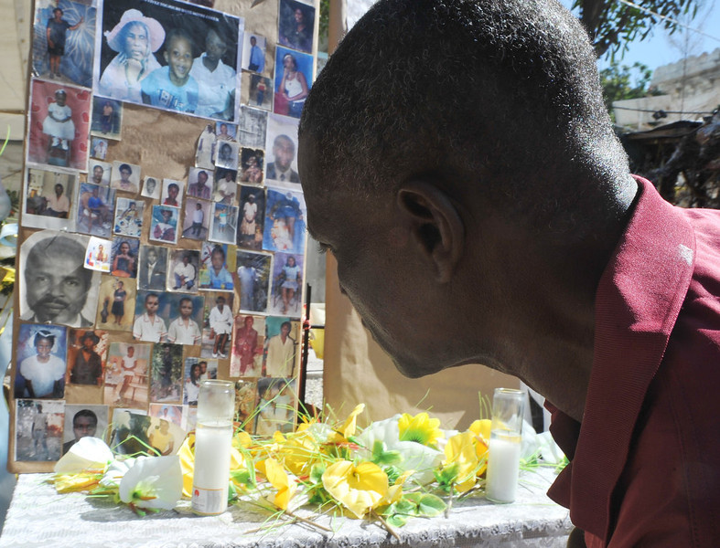 . A man pays his respects at a makeshift memorial for victims of the January 12, 2010 Haiti earthquake near the destroyed Cathedral of Port-au-Prince on January 12, 2013. Three years after a massive earthquake ravaged Haiti, President Michel Martelly said the country was slowly rebuilding, despite the ongoing day-to-day misery of many survivors.  An estimated 250,000 people were killed in the January 12, 2010 earthquake. Hundreds of thousands are still living rough in squalid makeshift camps, and they now face rampant crime, a cholera outbreak and the occasional hurricane.during memorial day in honor of the victims of the last quake of January 12 2013 in Haiti.People put photo of parent and friend victims of the quake. THONY BELIZAIRE/AFP/Getty Images