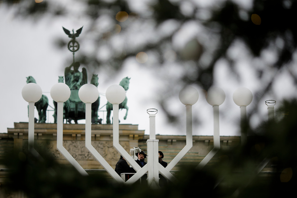 . Rabbi Yehuda Teichtal, center, and Rabbi Segal Shmoel, right, inspect with a construction worker a giant Hanukkah Menorah, set up by the Jewish Chabad Educational Center, at the Pariser Platz in Berlin, Tuesday, Dec. 12, 2017. (AP Photo/Markus Schreiber)