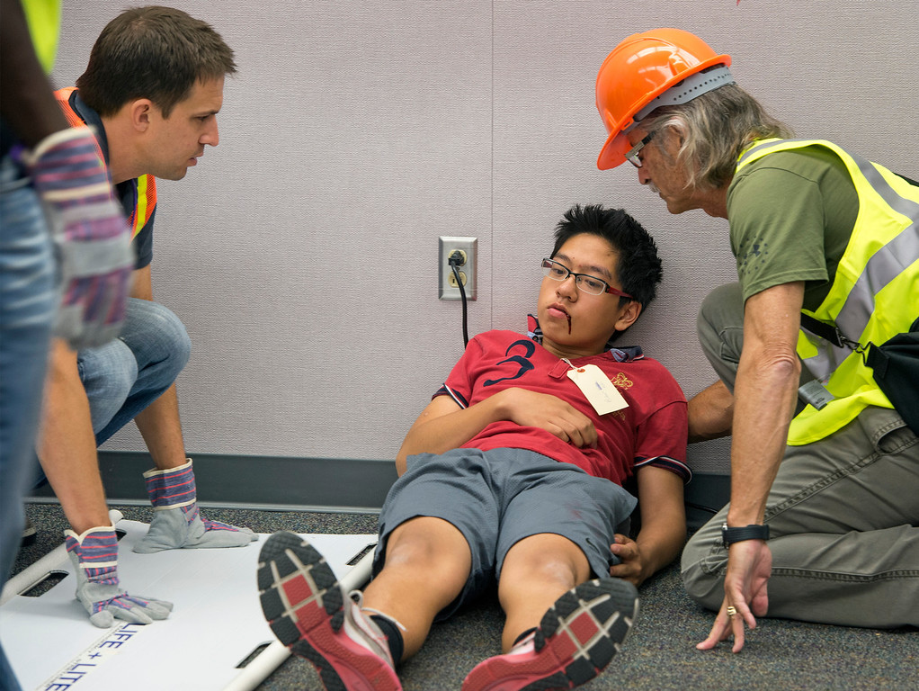 ". Diamond Bar High staff members Ryan Maine, left, and David Hamel evaluate an ""injured\"" student before taking him to triage during the Great ShakeOut earthquake drill at the Diamond Bar campus October 17, 2013.  (Staff photo by Leo Jarzomb/SGV Tribune)"